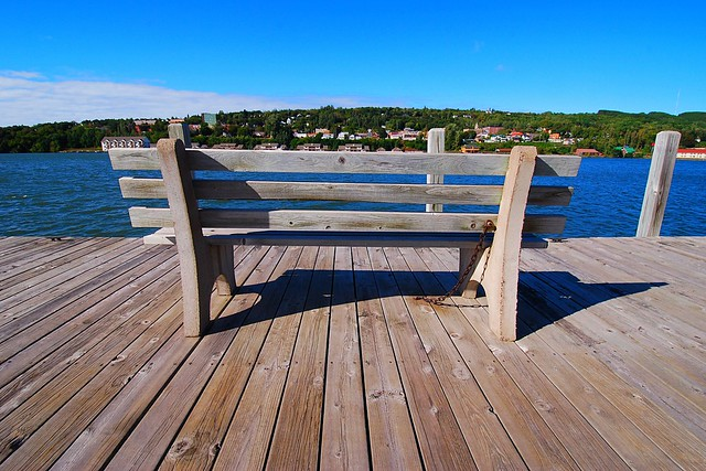 Wide view of a bench on a boardwalk, near the Portage waterway.