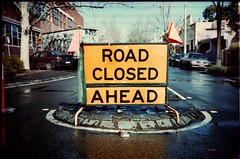 signs of closure (mugley) Tags: road trees orange signs cars film wet rain ahead yellow corner truck 35mm buildings xpro crossprocessed minolta suburban roadworks fitzroy australia melbourne slide victoria flags scan epson pointandshoot suburbs parked konica 135 roadclosed agfa urbanlandscape c41 precisa webbst agfactprecisa100 v700 ctprecisa100 trafficisland gorest freedomzoom160 rivazoom160 minoltafreedomzoom160
