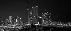 Skyline of Downtown Toronto (mainone) Tags: city longexposure bw white toronto ontario canada black building tower skyline architecture night cn train canon eos long exposure cntower nightshot go tracks sigma stadt 7d huge sw weiss schwarz gotrain kanada mainone 18250mm mainonech