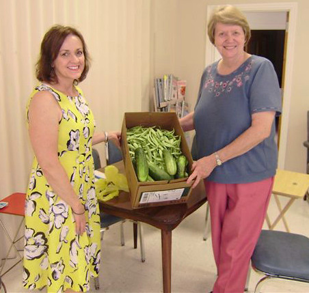 Lyda Ward, Director of Johnson County Senior Citizen and Adult Day Care Center,(right) accepting the beans and cucumbers donated by the USDA West Liberty Service Center from their people's garden for the seniors on July 6, 2010.