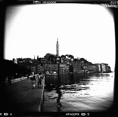Rovinj (Rolf F.) Tags: camera old city sunset urban blackandwhite bw sun building bird tower 120 film church monochrome birds silhouette architecture backlight analog canon mediumformat toy evening town holga fuji kodak roman stock n croatia scan d76 plastic explore 400 fujifilm neopan analogue expired rovigno rovinj canoscan istria hrvatska 120n stamm istra holga120cfn kroatien 8800 cfn istrien 8800f fujifilmneopan400