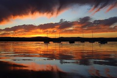 Flames (pominoz) Tags: sunset lake reflection clouds boats nsw reflexions lakemacquarie eleebana