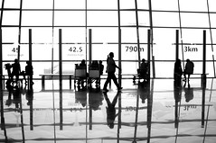 Beijing airport silhouettes (5ERG10) Tags: china travel bw white black reflection glass sergio lines vertical horizontal architecture 35mm walking person mirror hall airport nikon waiting holidays sitting squares beijing silhouettes august aeroporto terminal bn international national handheld   nikkor f18 departures bianco nero architettura cina peking checkin 2010 riflesso shunyi d300 pechino  bcia  amiti 5erg10