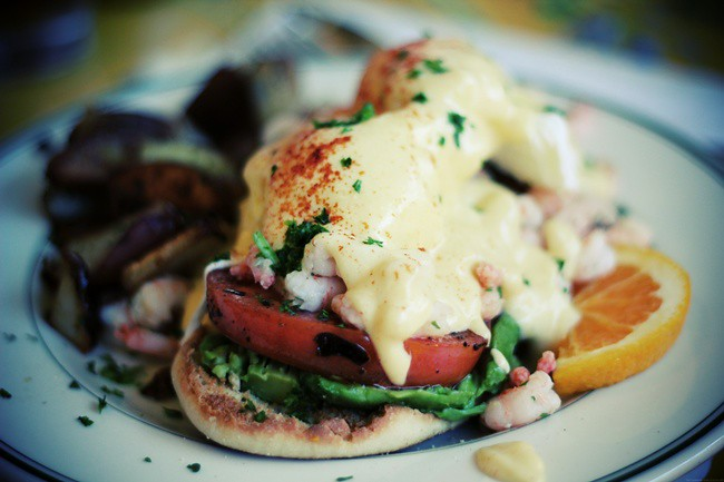 eggs benedict with shrimp, avocado and grilled tomato.