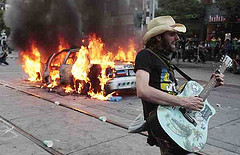 A police car burns while a protester plays at the Toronto G20 summit.