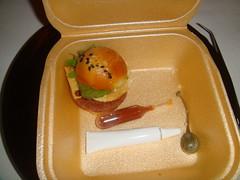 Hamburguesa con una galletita de queso, alcaparra, hoja de albahaca, aro de cebolla