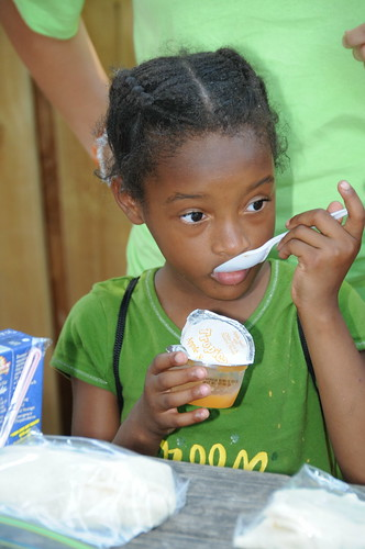 A little girl enjoys her applesauce which was part of her Summer Food Service Program meal at Light of the Village in Prichard, Ala., July 8.
