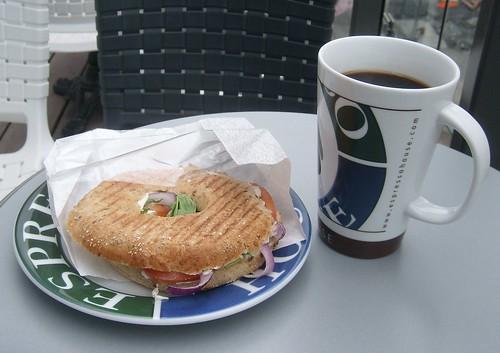 Varm bagel och en kopp kaffe