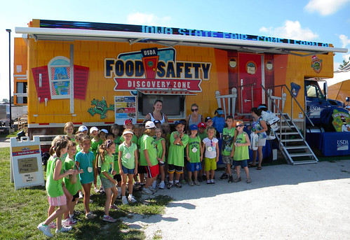 A school group poses in front of the Food Safety Discovery Zone after learning to Clean, Separate, Cook, and Chill.