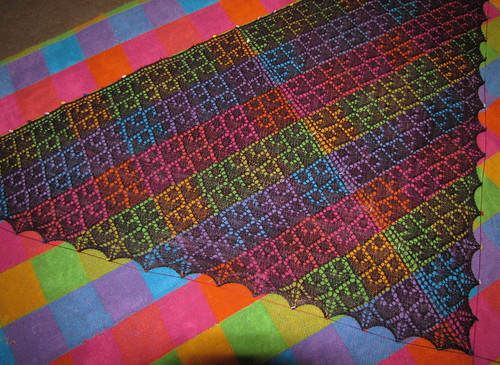 lace shawl pinned out on a bright plaid blanket