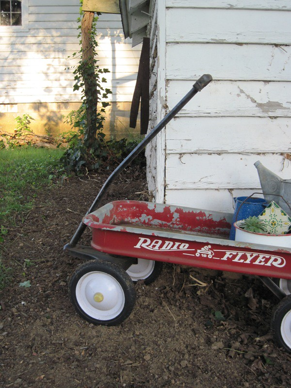 Radio Flyer in front of well house