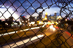 Fenced In, Part 2 (gomattolson) Tags: city minnesota skyline fence downtown bokeh dusk minneapolis twincities 35w
