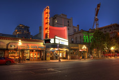 The Odeon Theater (HDR) (Brandon Godfrey) Tags: street city blue light urban canada colors st buildings twilight construction colorful theater neon cityscape colours bc crane britishcolumbia sony trails victoria hour western pacificnorthwest northamerica colourful alpha dslr juliet atrium hdr highdynamicrange yates scarface a300 photomatix theodeon