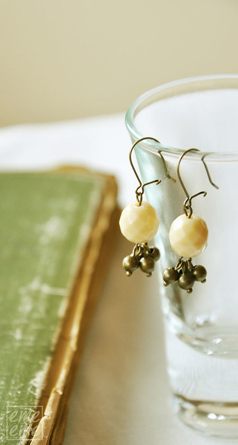 Creme color faceted glass bead and antique gold-plated brass earrings