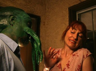 Heidi Martinuzzi campily cringes from the advances of a green, tentacled-face alien man