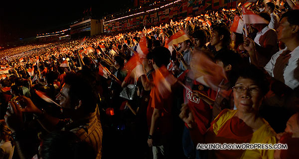 Audience proudly waving their Singapore flags