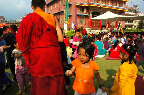 Tibetan children in bright colors are given nectar from the Hevajra initiation by a monk, under the large tent sit hundreds of people overflowing from the monastery, prayer flag, Buddhist flag, Tharlam Monastery courtyard, Boudha, Kathmandu, Nepal by Wonderlane