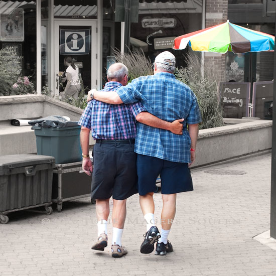 Two men in blue plaid venture off from their wives in a brotherly embrace to share a moment of friendship.