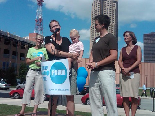 Jen Harvey, Chris Harper Patterson and their child speaking at the One Iowa rally in Des Moines