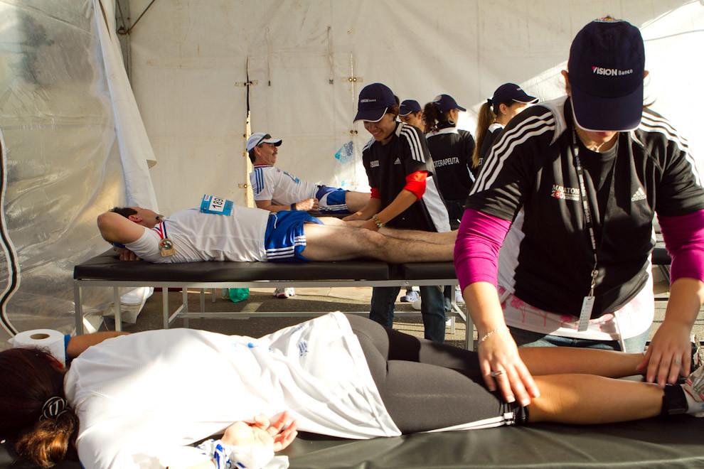 Un atleta recibe masajes luego de terminar la carrera, a manos de fisioterapeutas mujeres en uno de los toldos de atención medica. (Tetsu Espósito - Asunción, Paraguay)