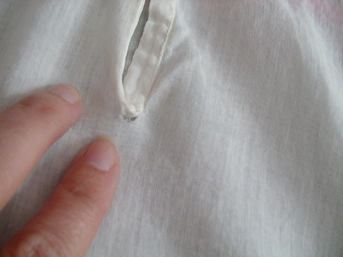 tear at back on button placket.