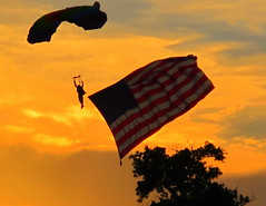 July 4th 2010 Fireworks show with skydiver landing at sunset with American Flag in Austin, Texas, USA (ggarner) Tags: birthday sunset red usa white austin texas fireworks flag celebration july4th july4 independenceday celebrate skydiver oldglory andblue happybirthdayamerica top25redorangeyellow