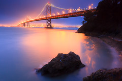 The Bay Bridge...illuminated (Jared Ropelato) Tags: ocean sanfrancisco california city longexposure trip travel bridge light sea wild vacation sky nature beautiful beauty rock fog night clouds canon landscape island photography lights oakland bay site rocks waves cityscape treasure treasureisland pacific crash outdoor tripod rustic scenic illumination wave visit scene hike cliffs trail filter baybridge flare bayarea wilderness rugged illuminate manfrotto 2010 giotto cablerelease 1635mm singhray 5dmkii jaredropelato ropelatophotography