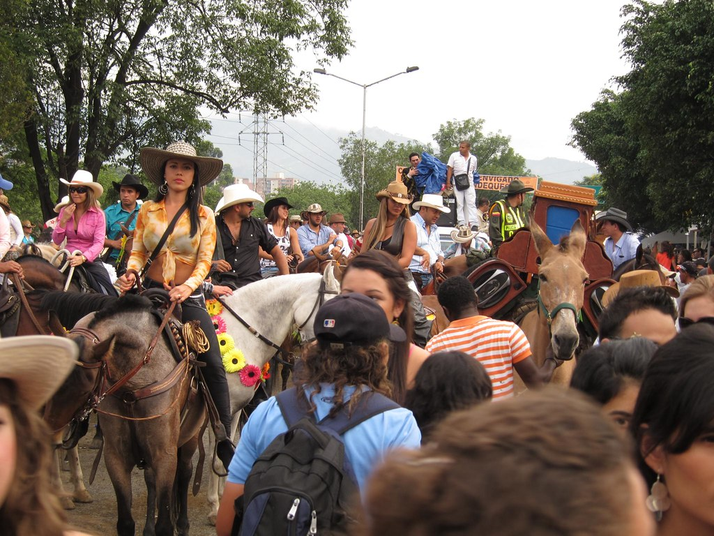 The parade route was congested with a mix of horses, people, and trucks.