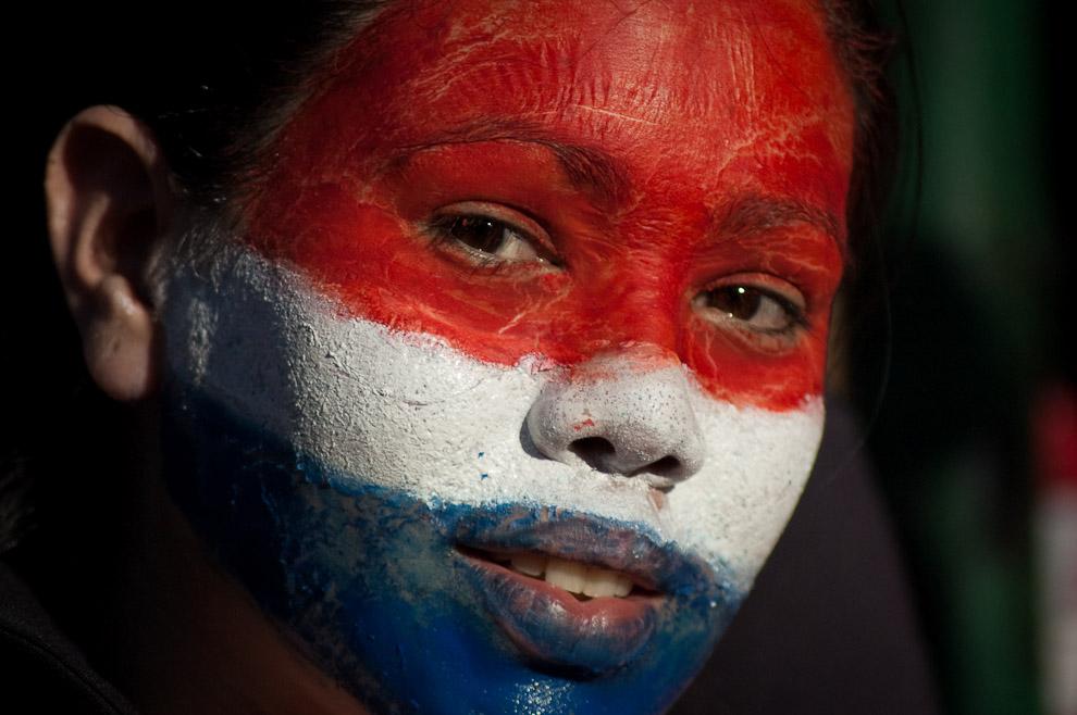 Una niña Paraguaya pinta su rostro con los colores de la bandera Paraguaya en la Plaza de la Democracia (Elton Núñez - Asunción, Paraguay)