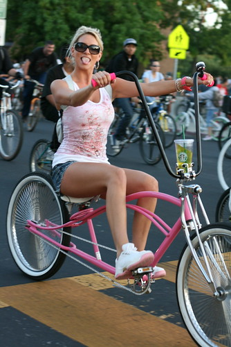 girl in short shorts on pink bicycle