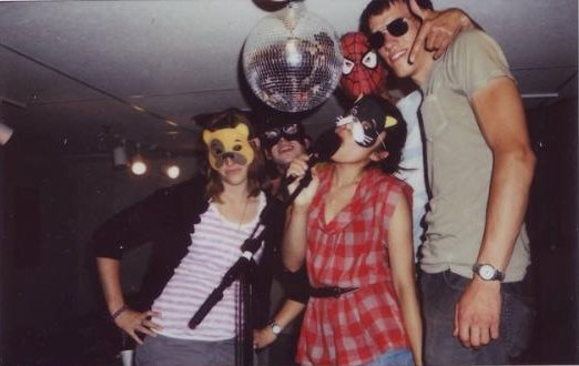 Five young people, including two women, mostly wearing masks, grin candidly under a disco ball into a polaroid camera