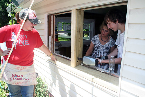 Volunteers nail down window frame