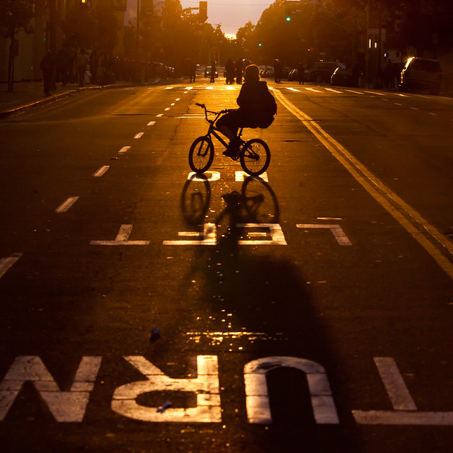 Protestor on Bicycle With Riot Cops in Distance as Sun Begins to Set, Oakland Riots, 2010