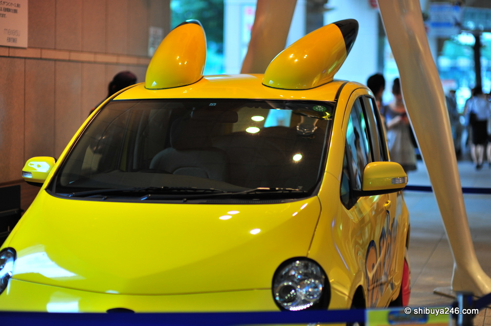 a pikachu car at the feet of Jane