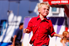 Boy Running Through the Midway, Missoula County Fair (CT Young) Tags: montana streetphotography fair missoula countyfair streetshot gardencity streetcandid missoulamt missoulamontana streetshooting westernmontanafair missoulacountyfair canonefs55250mmf456is westernmontanafair2010