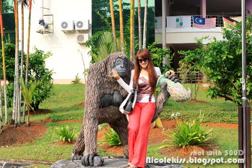 posing with orang utan statue