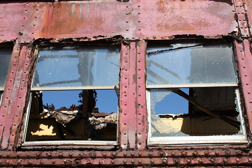 A view of the inside of an abandoned train car, showing shadows cast by holes in the roof.
