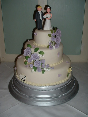 3 tiered wedding cake with lilac roses and premade bride and groom wedding