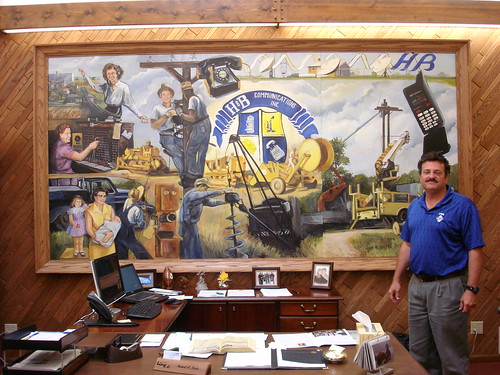 Robert Koch, President and General Manager of H&B Communications in Holyrood, Kansas, stands in front of a mural highlighting milestones in his family's telecommunications business.