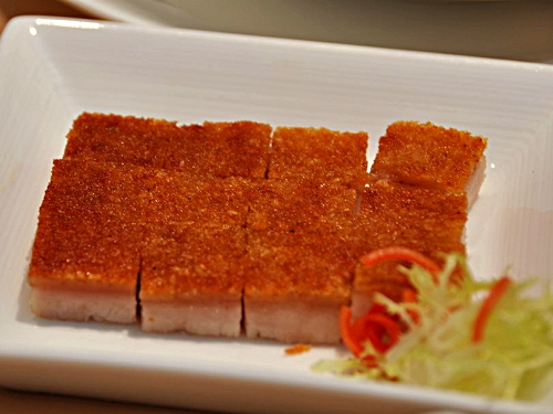 A dozen squares of roast belly pork with golden-coloured crackling, arranged neatly in a white rectanglar dish garnished with a small clump of shredded lettuce and carrots.