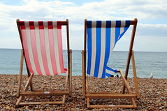 Beach Seating (Irene Stylianou) Tags: ocean uk greatbritain blue red sea summer vacation england sky bird beach clouds pier sand nikon holidays rocks brighton europe chairs unitedkingdom stripes seagull bluesky pebbles seats nikkor seating nikondigital eastsussex vr brightonpier d300 saeside nikoncamera travelphotography 18200mm vr2 nikkor18200mm officialnikkor nikond300 irenestylianou nikkorzoomlens18200mmf3556