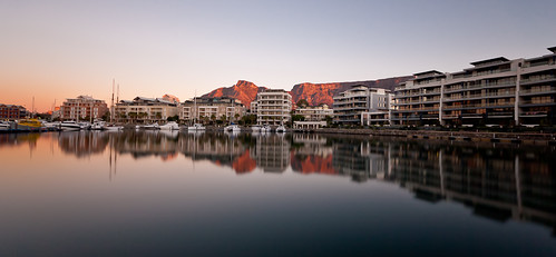 Apartment blocks in the V&A Waterfront reflected in the water with Table Mountain in the background paionted red by the setting sun.