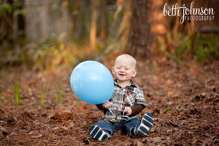 first birthday boy with blue balloon