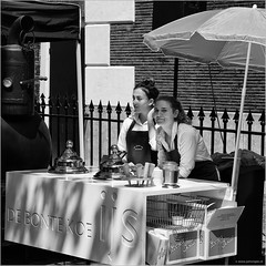 Icecream girls (John Riper) Tags: johnriper street photography straatfotografie schiedam square bw black white zwartwit mono monochrome netherlands candid john riper canon 6d 24105 l cultural event jenever genever gin jeneverfestival bonte koe chocola ijs chocolate icecream stall parasol girls eye contact looses biscuit cornetto