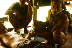 Cale beind healed by Tarason, Mentawai shaman (joeyL.com) Tags: lighting tattoo ferry trekking indonesia boat rainforest photoshoot battery uma culture photographers tourists generator western hunter guide explorers healing behindthescenes ricky travelers translator shamanism solarpower sacrafice gatherer joeylawrence profoto elinchrom joeyl mentawai siberut caleglendening gejeng willemisbrucker