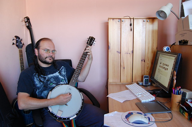 Self-portrait: Wulf playing guitjo, seated at his home workstation