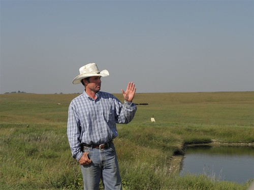 Dan Imthurn stands by lagoon, a part of his agricultural waste system, with rangeland behind him. Dan captures the wastes from his feedlot and applies the manure to his land as a fertilizer. His efforts protect the water quality in nearby Mill Creek while improving the productivity of his land.