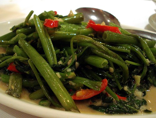 Slim hollow green stems of stirfried water spinach are piled on a plate, glistening with liquid.  Several shreds of red chilli are tucked among them, and a pool of light creamy sauce has gathered on the base of the plate.