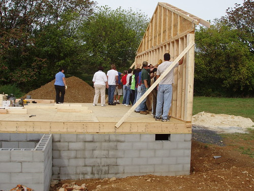 Volunteers secure the north end wall of the house after it is lifted into place.