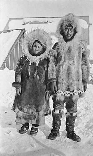 Eskimo couple wearing fur parkas and mukluks standing in snow with buildings in background